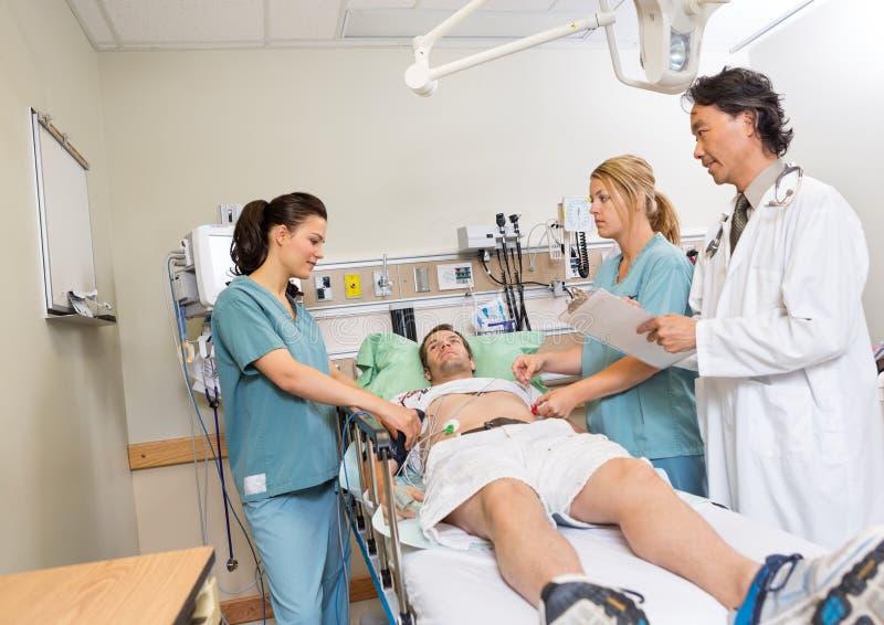 Γιατρός και νοσοκόμες που ελέγχουν τον ασθενή στο νοσοκομείο στοκ εικόνα με δικαίωμα ελεύθερης χρήσης
