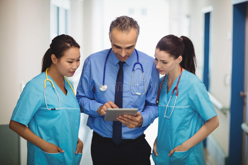 Γιατρός και νοσοκόμες που συζητούν πέρα από την ψηφιακή ταμπλέτα στοκ φωτογραφίες με δικαίωμα ελεύθερης χρήσης