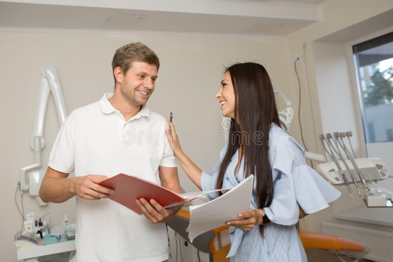 Γιατρός και ο βοηθός του που κοιτάζουν στο φάκελλο με το έγγραφο Οδοντικό υπόβαθρο γραφείων στοκ εικόνες