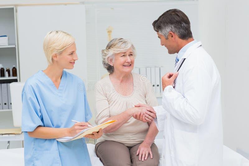 Γιατρός και υπομονετικά χέρια τινάγματος ενώ το γράψιμο νοσοκόμων υποβάλλει έκθεση στοκ εικόνα με δικαίωμα ελεύθερης χρήσης
