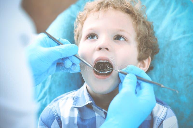 Γιατρός και υπομονετικό παιδί Αγόρι που έχει τα δόντια του εξετασμένων με την ιατρική οδοντιάτρων, την υγειονομική περίθαλψη και  στοκ φωτογραφίες