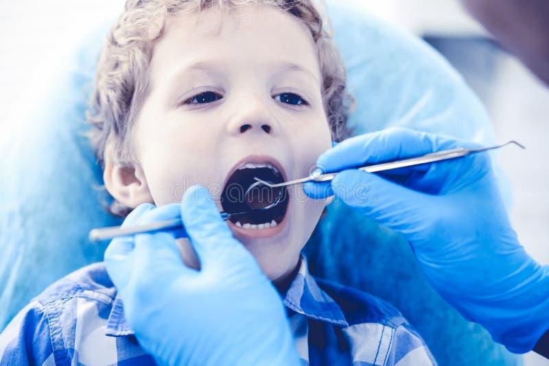 Γιατρός και υπομονετικό παιδί Αγόρι που έχει τα δόντια του εξετασμένων με την ιατρική οδοντιάτρων, την υγειονομική περίθαλψη και  στοκ φωτογραφία με δικαίωμα ελεύθερης χρήσης
