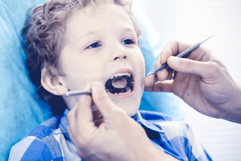 Γιατρός και υπομονετικό παιδί Αγόρι που έχει τα δόντια του εξετασμένων με την ιατρική οδοντιάτρων, την υγειονομική περίθαλψη και  στοκ εικόνες