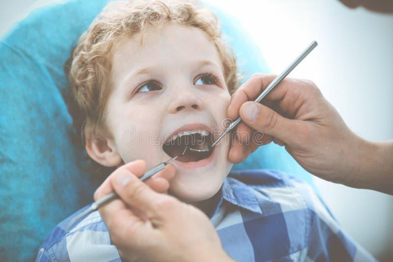 Γιατρός και υπομονετικό παιδί Αγόρι που έχει τα δόντια του εξετασμένων με την ιατρική οδοντιάτρων, την υγειονομική περίθαλψη και  στοκ φωτογραφία