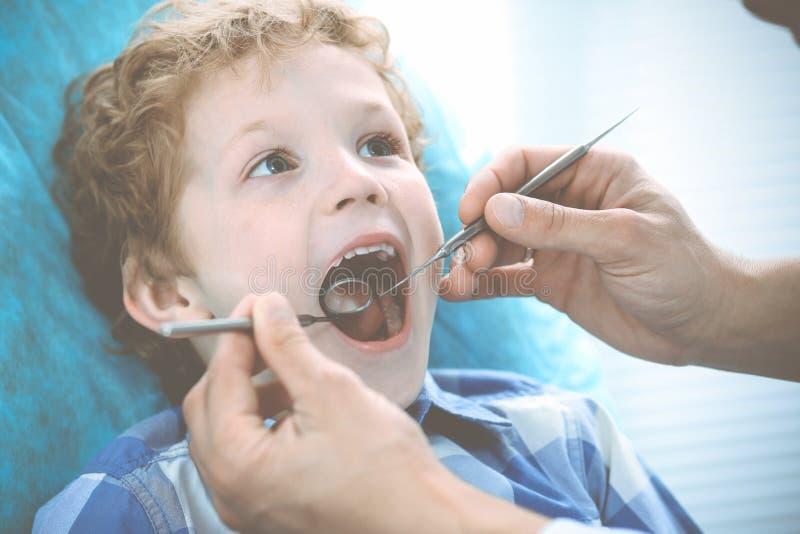 Γιατρός και υπομονετικό παιδί Αγόρι που έχει τα δόντια του εξετασμένων με την ιατρική οδοντιάτρων, την υγειονομική περίθαλψη και  στοκ εικόνα