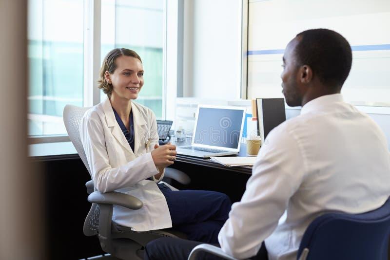 Γιατρός κατόπιν διαβουλεύσεων με τον αρσενικό ασθενή στην αρχή στοκ εικόνα με δικαίωμα ελεύθερης χρήσης