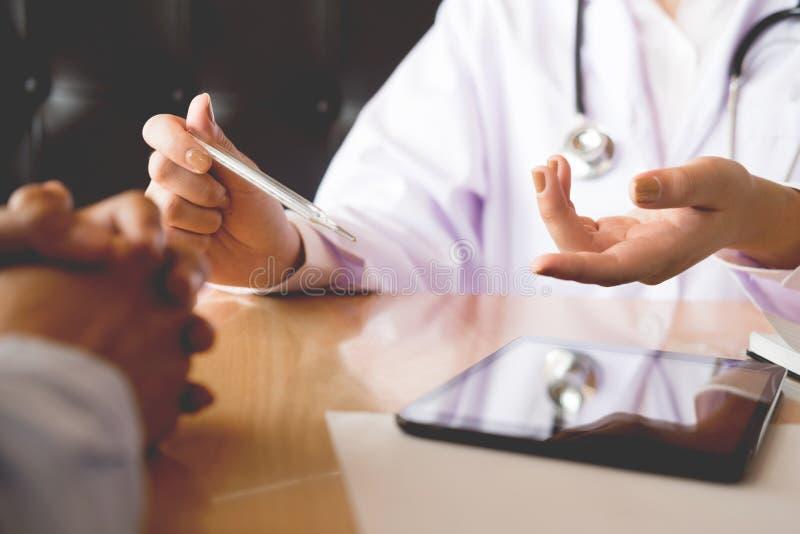 Γιατρός με ένα θερμόμετρο στο χέρι του που παίρνει υπομονετικό ` s στο νοσοκομείο, ιατρική έννοια στοκ φωτογραφία