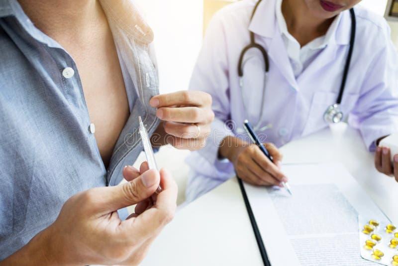 Γιατρός με ένα θερμόμετρο στο χέρι του που παίρνει υπομονετικό ` s στο hospit στοκ φωτογραφία με δικαίωμα ελεύθερης χρήσης