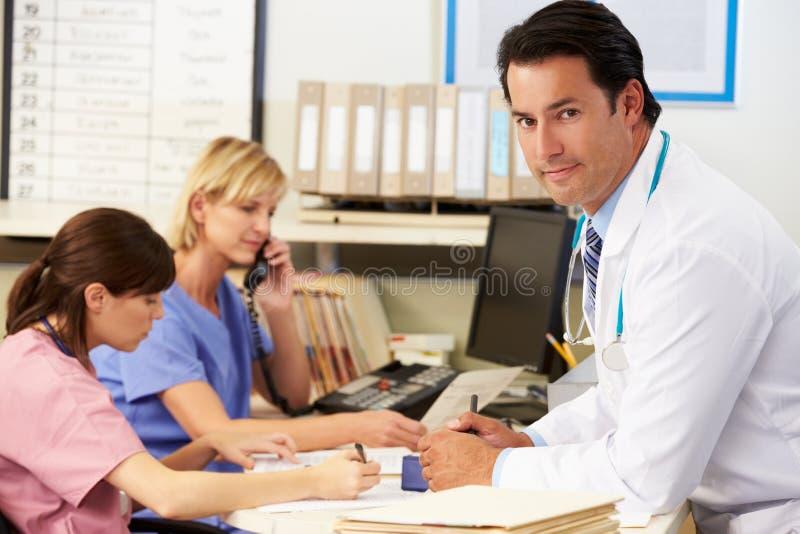 Γιατρός με δύο νοσοκόμες που εργάζονται στο σταθμό νοσοκόμων στοκ εικόνες