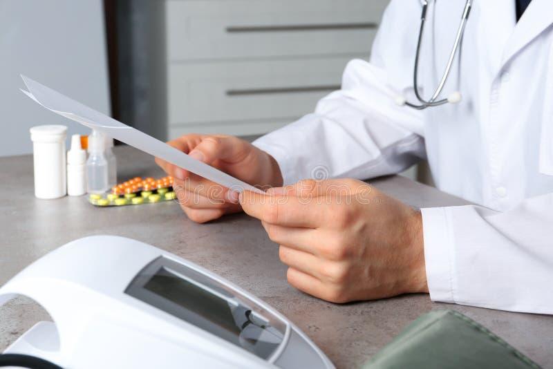 Γιατρός με τα έγγραφα και ψηφιακός μετρητής πίεσης στον πίνακα ιατρικά αντικείμενα στοκ εικόνα με δικαίωμα ελεύθερης χρήσης