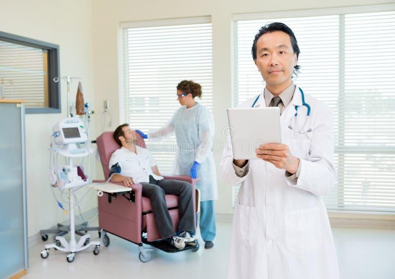 Γιατρός με την ψηφιακή ταμπλέτα στο δωμάτιο Chemo στοκ φωτογραφίες