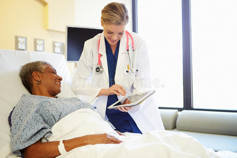 Γιατρός με τις ψηφιακές συζητήσεις ταμπλετών στη γυναίκα στο νοσοκομειακό κρεβάτι στοκ εικόνες με δικαίωμα ελεύθερης χρήσης