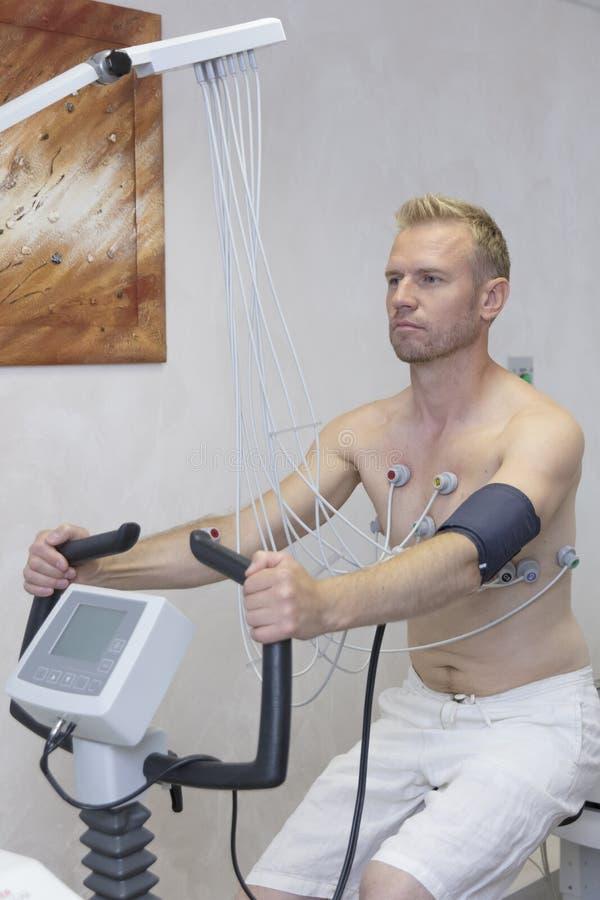 Γιατρός με τον εξοπλισμό ηλεκτροκαρδιογραφημάτων που κάνει το καρδιογράφημα υπό δοκιμή φορτίων στον αρσενικό ασθενή στην κλινική  στοκ φωτογραφία