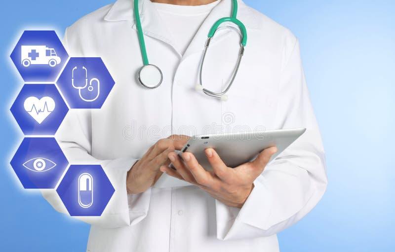 Γιατρός με το στηθοσκόπιο και ταμπλέτα στο υπόβαθρο χρώματος Σε απευθείας σύνδεση ιατρική υπηρεσία στοκ εικόνες με δικαίωμα ελεύθερης χρήσης