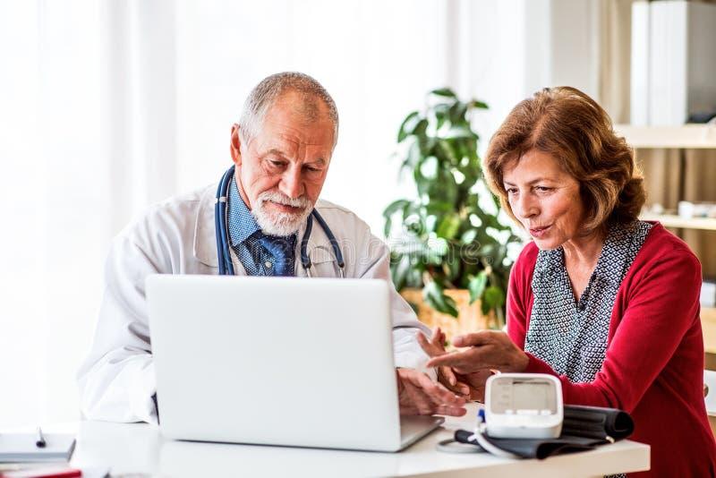 Γιατρός με το lap-top που μιλά σε μια ανώτερη γυναίκα στην αρχή στοκ φωτογραφία