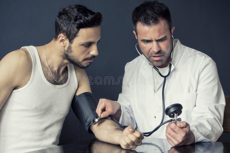 Γιατρός με το sphygmomanometer που ελέγχει το σφυγμό από τον ασθενή στοκ εικόνες