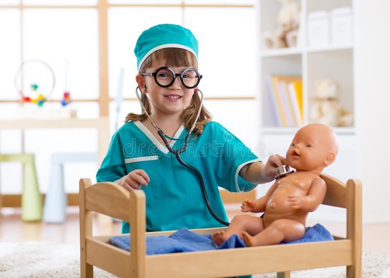 Γιατρός παιδικών παιχνιδιών με το μωρό - κούκλα στο βρεφικό σταθμό στοκ φωτογραφία με δικαίωμα ελεύθερης χρήσης