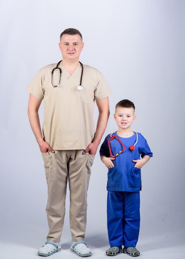 Γιατρός πατέρων με το στηθοσκόπιο και λίγος παθολόγος γιων ομοιόμορφος m Θελήστε να είστε γιατρός ως μπαμπά Χαριτωμένο παιδί στοκ φωτογραφία