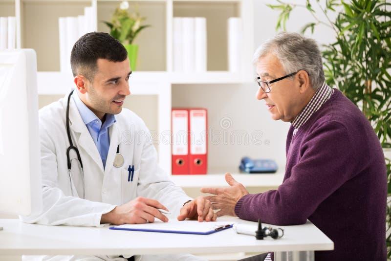 Γιατρός που ακούει υπομονετικό εξηγώντας επίπονό του στοκ εικόνα