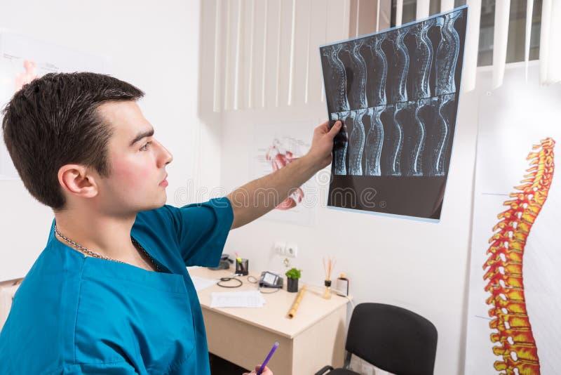 Γιατρός που αναλύει την εικόνα ακτίνας X της ανθρώπινης σπονδυλικής στήλης στοκ φωτογραφία