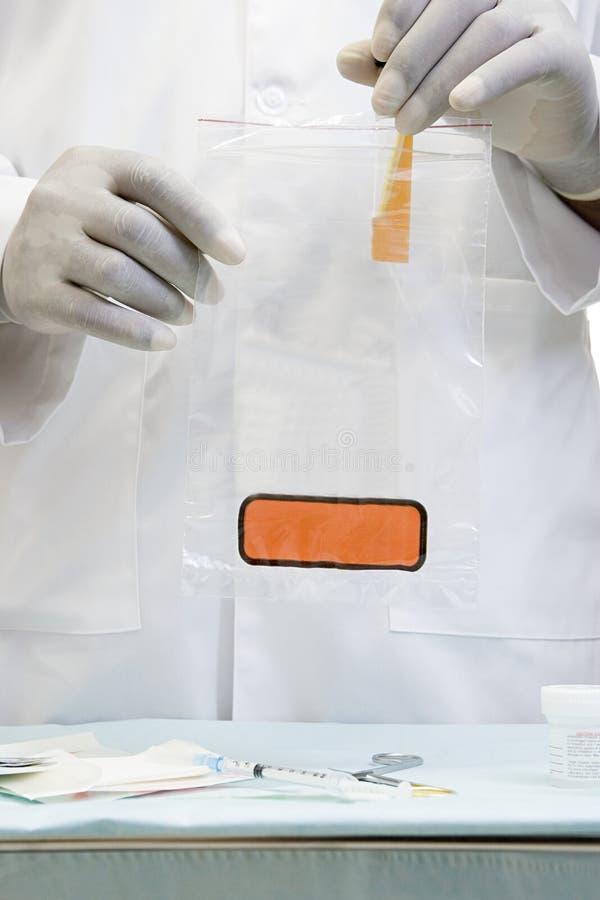 Γιατρός που βάζει ένα δείγμα στην τσάντα biohazard στοκ φωτογραφία με δικαίωμα ελεύθερης χρήσης