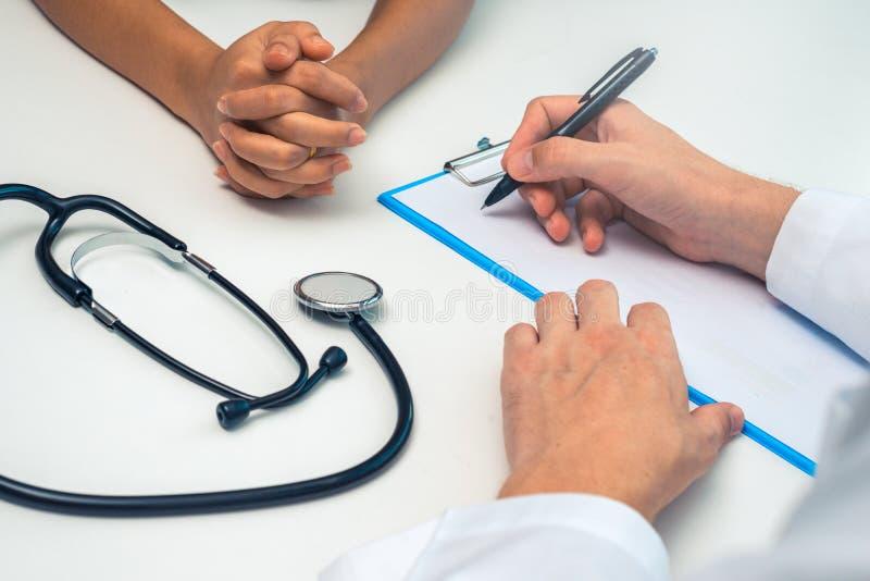 Γιατρός που γράφει μια ιατρική συνταγή για έναν ασθενή γυναικών στοκ εικόνες