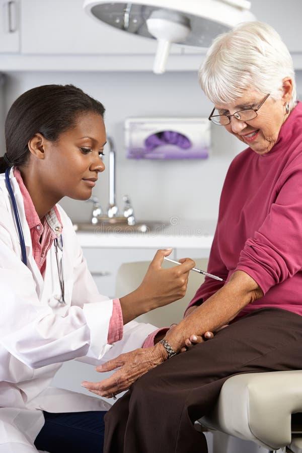 Γιατρός που δίνει την ανώτερη θηλυκή υπομονετική έγχυση στοκ εικόνα