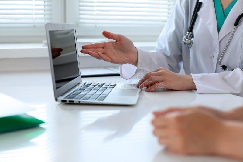 Γιατρός που δείχνει στο φορητό προσωπικό υπολογιστή και που συζητά κάτι με τον ασθενή της Κινηματογράφηση σε πρώτο πλάνο στοκ εικόνα