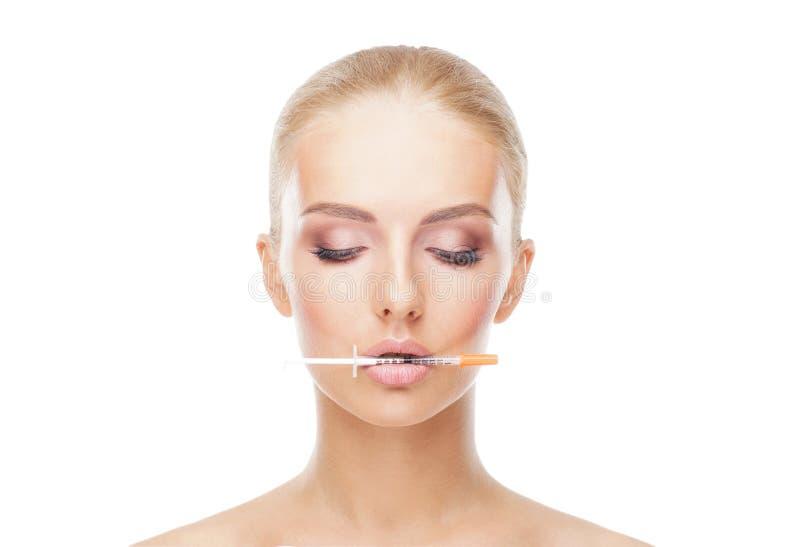 Γιατρός που εγχέει σε ένα όμορφο πρόσωπο μιας νέας γυναίκας απομονωμένο έννοια λευκό πλαστικής χειρουργικής στοκ φωτογραφία