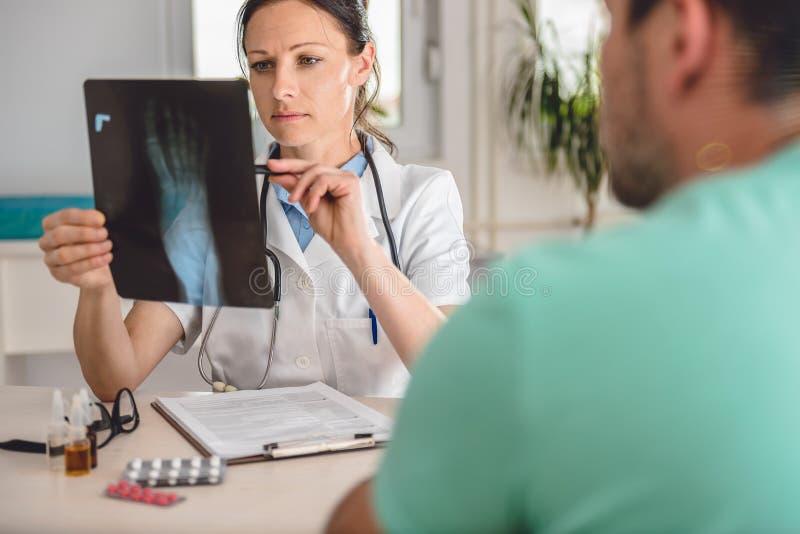 Γιατρός που ελέγχει την ακτίνα X αστραγάλων στοκ εικόνες