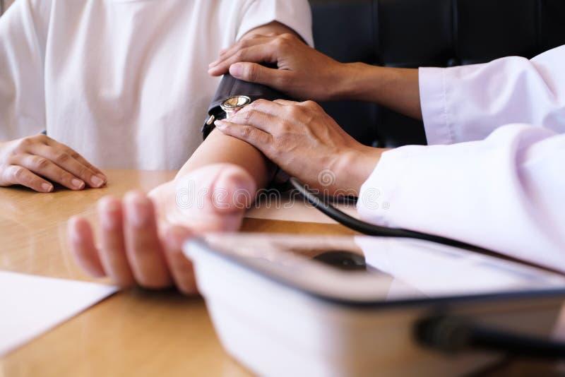 Γιατρός που ελέγχει την υπομονετική αρτηριακή πίεση του αίματος η υγεία προσοχής όπλων απομόνωσε τις καθυστερήσεις στοκ εικόνες με δικαίωμα ελεύθερης χρήσης