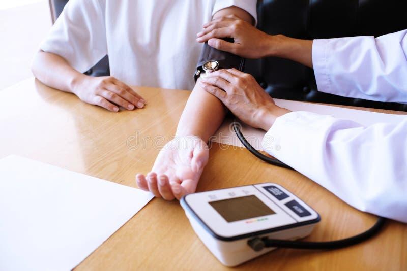 Γιατρός που ελέγχει την υπομονετική αρτηριακή πίεση του αίματος η υγεία προσοχής όπλων απομόνωσε τις καθυστερήσεις στοκ εικόνες