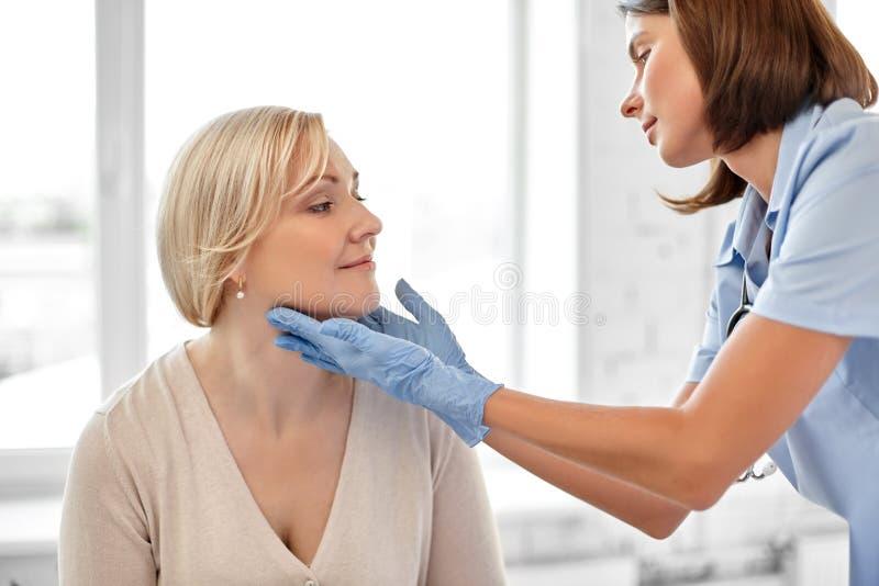 Γιατρός που ελέγχει τις αμυγδαλές του ασθενή στο νοσοκομείο στοκ εικόνα