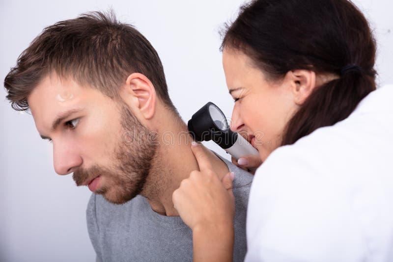 Γιατρός που ελέγχει το δέρμα στον ανθρώπινο λαιμό στοκ φωτογραφία