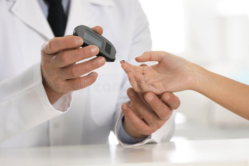 Γιατρός που ελέγχει το επίπεδο ζάχαρης αίματος του ασθενή με το ψηφιακό glucometer στον πίνακα, κινηματογράφηση σε πρώτο πλάνο στοκ εικόνα