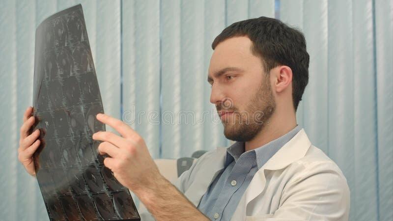 Γιατρός που εξετάζει μια ακτίνα X στο γραφείο της στοκ εικόνες