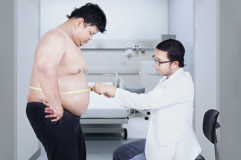Γιατρός που εξετάζει μια υπομονετική παχυσαρκία στοκ εικόνες