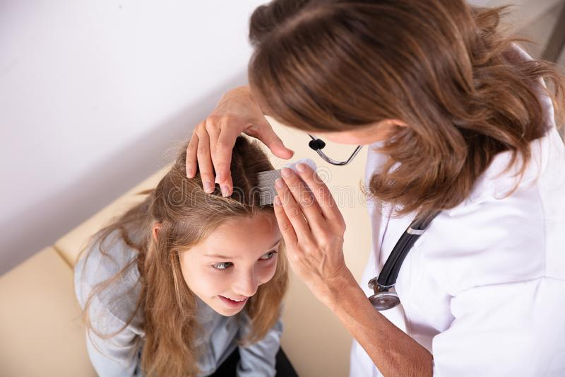 Γιατρός που εξετάζει την τρίχα του κοριτσιού στοκ εικόνες