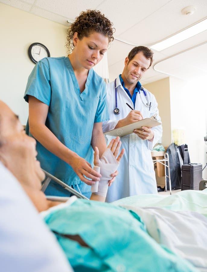 Γιατρός που εξετάζει τη νοσοκόμα που βάζει τον επίδεσμο στον ασθενή στοκ φωτογραφία