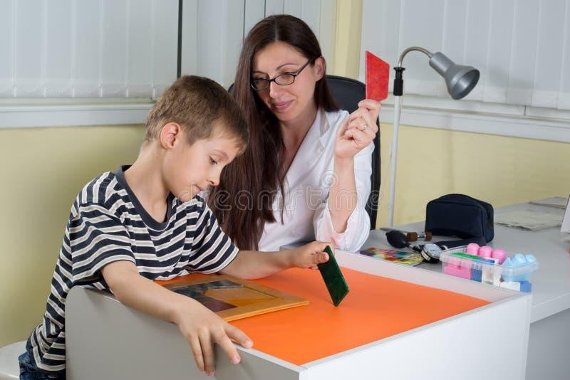 Γιατρός που εξετάζει τη λογική σκέψη του μικρού παιδιού με τις χρωματισμένες γεωμετρικές μορφές στη διαβούλευση του δωματίου στοκ εικόνες