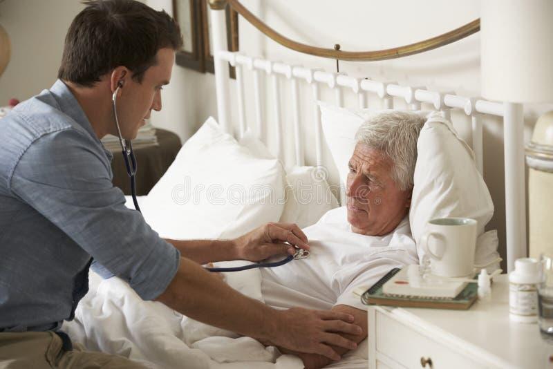 Γιατρός που εξετάζει τον ανώτερο αρσενικό ασθενή στο κρεβάτι στο σπίτι στοκ εικόνες
