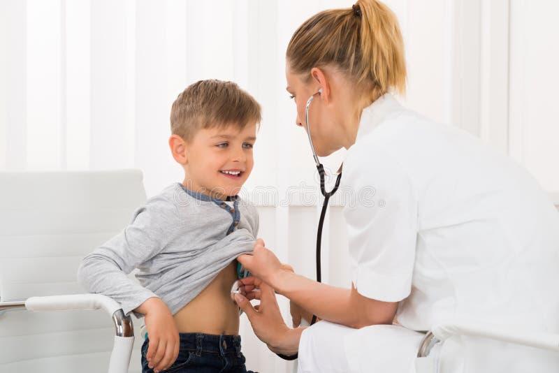 Γιατρός που εξετάζει το αγόρι στην κλινική στοκ εικόνα