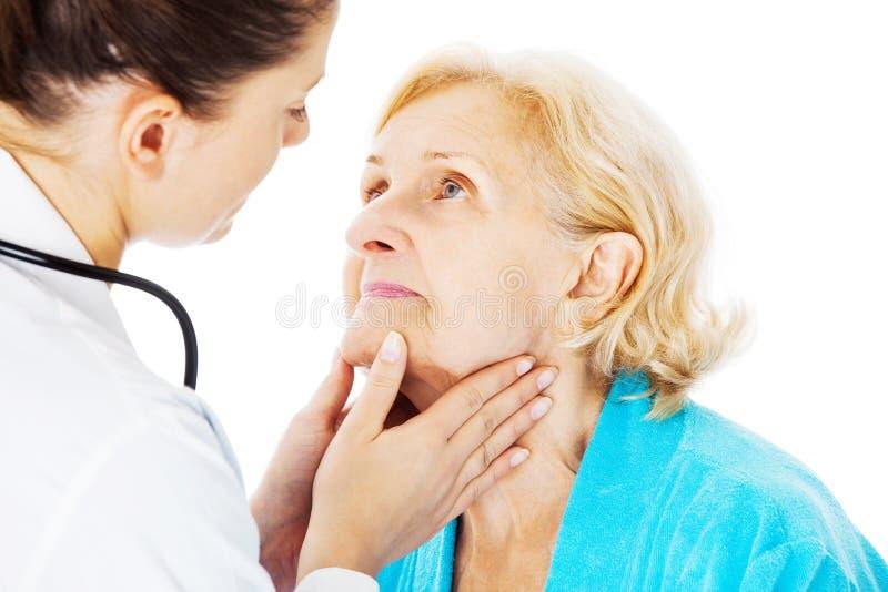 Γιατρός που εξετάζει το λαιμό της ανώτερης γυναίκας στοκ εικόνες με δικαίωμα ελεύθερης χρήσης