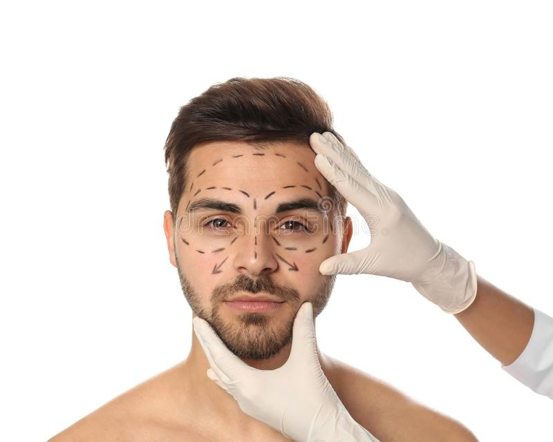 Γιατρός που εξετάζει το ανθρώπινο πρόσωπο με τις γραμμές δεικτών για τη λειτουργία πλαστικής χειρουργικής στο λευκό στοκ εικόνα με δικαίωμα ελεύθερης χρήσης