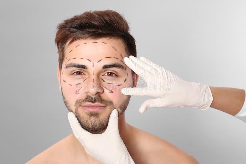 Γιατρός που εξετάζει το ανθρώπινο πρόσωπο με τις γραμμές δεικτών για τη λειτουργία πλαστικής χειρουργικής στοκ εικόνες