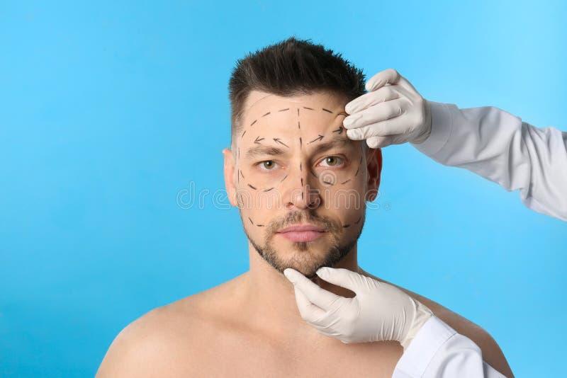 Γιατρός που εξετάζει το ανθρώπινο πρόσωπο πριν από τη λειτουργία πλαστικής χειρουργικής στοκ φωτογραφία με δικαίωμα ελεύθερης χρήσης