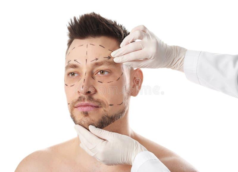 Γιατρός που εξετάζει το ανθρώπινο πρόσωπο πριν από τη λειτουργία πλαστικής χειρουργικής στοκ εικόνες με δικαίωμα ελεύθερης χρήσης