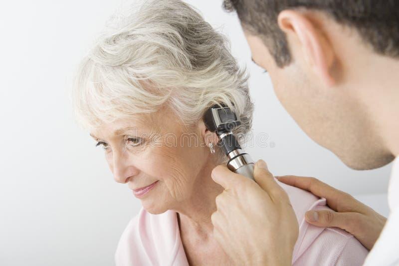 Γιατρός που εξετάζει το αυτί του ασθενή που χρησιμοποιεί το ωτοσκόπιο στοκ φωτογραφία με δικαίωμα ελεύθερης χρήσης