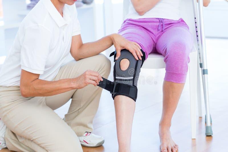 Γιατρός που εξετάζει το γόνατο ασθενών της στοκ εικόνες