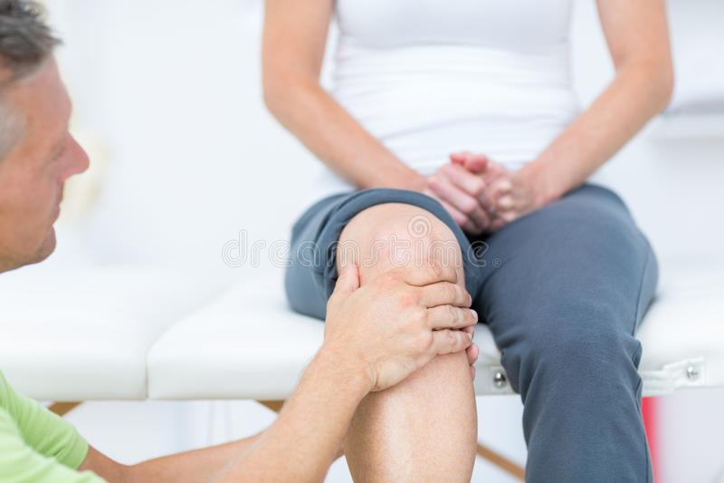 Γιατρός που εξετάζει το γόνατο ασθενών του στοκ εικόνες με δικαίωμα ελεύθερης χρήσης